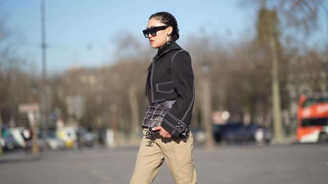 stockvideo's en b-roll-footage met jaime xie wears sunglasses a black turtleneck top a denim jacket with shoulder pads a belt with metallic buckle beige pants a bag with chains cowboy... - coltrui