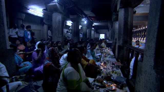 Jain women watch as a part of the Mahamastakabhisheka ritual is performed at the Shravanabelagola Temple. Available in HD.