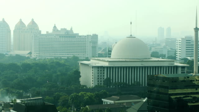 jakarta elevated skyline daytime with istiqlal mosque 4k video - smog stock videos & royalty-free footage