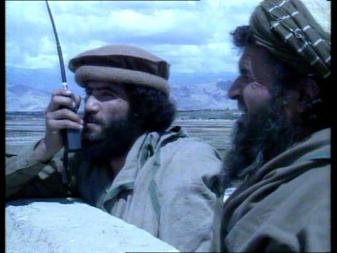 jalalabad ext soviet helicopter gunships in distance mujahideen with walkie talkie mortar fired hole made in wall and rpg7 fired plume of smoke... - afghanistan stock videos & royalty-free footage