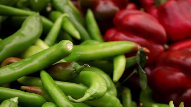 jalapeno peppers and red bell peppers fill a bin at the ben yehuda market in jerusalem - peperone video stock e b–roll