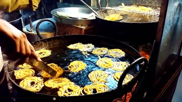 jalebi (tangled food tubes filled with sweet syrup) is cooking in oil - ゼンタングル模様点の映像素材/bロール