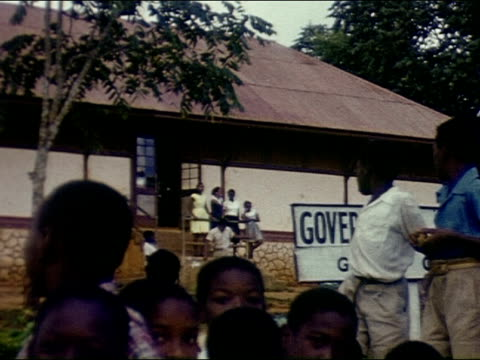 jamaican school children in uniforms outside government school / tourist women in flowered hats talk to them two women get out of pink golf cart one... - jamaican ethnicity stock videos and b-roll footage