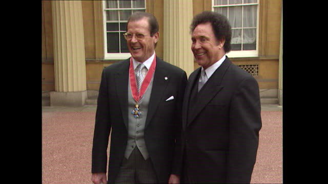 james bond actor roger moore with welsh singer tom jones at buckingham palace in london after they each received honours from the queen. moore... - 俳優 ロジャー・ムーア点の映像素材/bロール