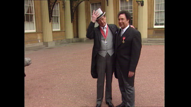James Bond actor Roger Moore with Welsh singer Tom Jones at Buckingham Palace in London after they each received honours from the Queen Moore...