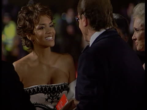 stockvideo's en b-roll-footage met james bond film premiere cf tape no longer available london royal albert hall ms actress halle berry kissing actor roger moore on cheek as arriving... - première