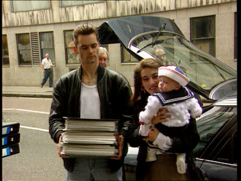 james bulger murderers; itn lib england: london: ext ralph and denise bulger with baby, michael, delivering petition to 10 downing st - 殺人者点の映像素材/bロール