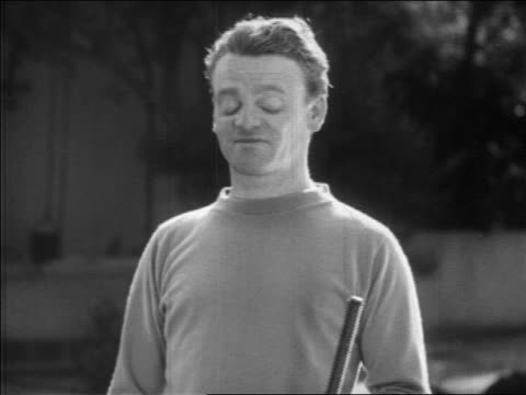 James Cagney making face tossing croquet mallet outdoors / newsreel