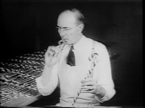 james cochrane pulling and twisting candy mixture / cochrane and assistant placing candy stripe on unfinished loaf of candy mixture / various angles... - candy cane stock videos & royalty-free footage