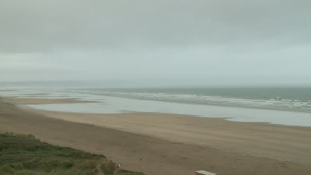 james cracknell and son rescue boy and his grandfather at devon beach; wide shot of deserted beach - オフビート点の映像素材/bロール