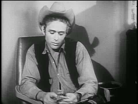 vídeos y material grabado en eventos de stock de james dean in cowboy hat looking down talking to someone off screen / psa - sólo hombres jóvenes
