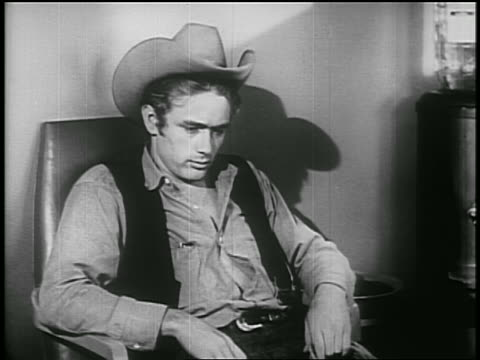 stockvideo's en b-roll-footage met james dean in cowboy hat sitting in chair talking to someone off screen / psa - 1955