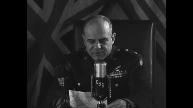 ls james doolittle in uniform sits at desk holding speech prepares to read into cbs microphone with american flag and union jack as backdrop / cu... - broadcasting stock videos and b-roll footage