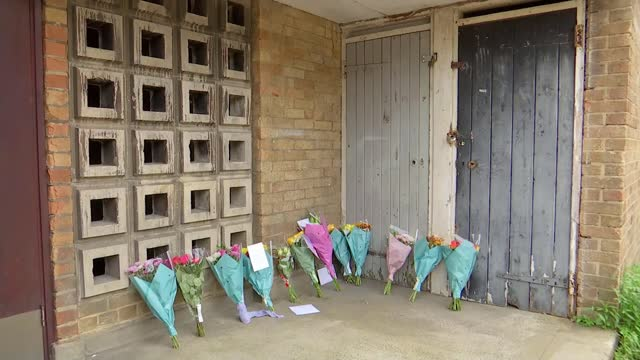 two teenagers arrested; england: london: chingford: ext woman laying flowers with others message attached to flowers various of police vans and... - crime and murder stock videos & royalty-free footage