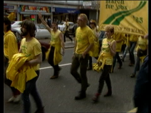james prior; james prior; itn lib ext herts: watford: tms vans in street followed by marching people in yellow carrying banners tms demonstraters... - ピーター・シソンズ点の映像素材/bロール