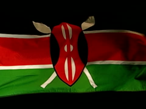 jamhuri y kenya country flag flying against black bg three horizontal bands black red green w/ red band edged in white decorated warrior shield in... - kenia stock-videos und b-roll-filmmaterial