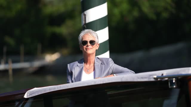 jamie lee curtis wears a necklace, sunglasses, a white t-shirt, a gray blazer jacket, and arrives at the 78th venice international film festival on... - celebrity sightings stock videos & royalty-free footage