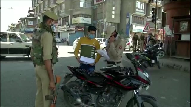 jammu & kashmir police standing on the road at srinagar's market area.police stopping vehicles on the road during lockdown and questioning drivers in... - pianificazione di emergenza video stock e b–roll