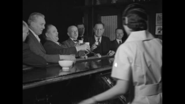stockvideo's en b-roll-footage met jampacked tavern with several steins being hoisted and four men at bar singing german song in fourpart harmony / note exact day not known - 1933