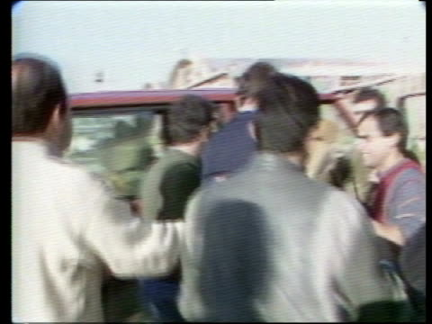 stockvideo's en b-roll-footage met ext / jan 1987 lebanon cms terry waite beirut special envoy chatting in crowd bv waite into range rover as crowd men behind him ms range rover along... - terry waite