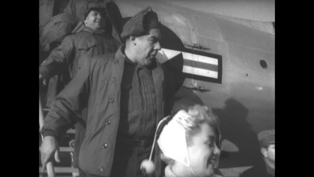 jan sterling and husband paul douglas walk down steps of military plane followed by other actors, wave, and pause at bottom of steps/ crowd on tarmac... - debbie reynolds stock-videos und b-roll-filmmaterial