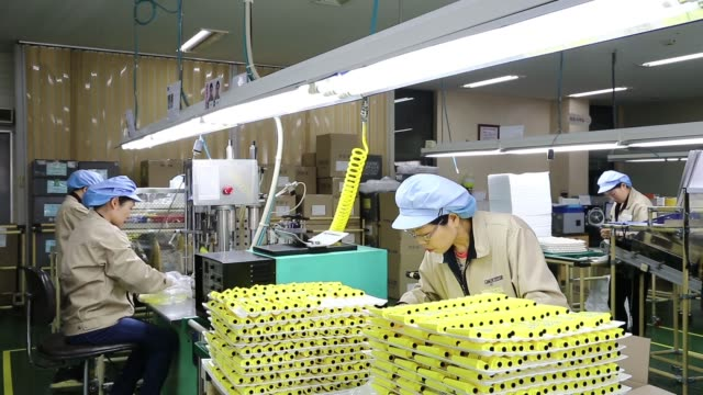 Jangup System Co employees inspect mascara containers on the production line for manufacturing cosmetics containers at the company factory in Yongin...