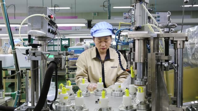 Jangup System Co employees put mascara containers into an assembly machine on the production line for manufacturing cosmetic containers at the...