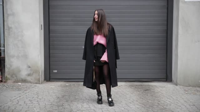 Janina Pfau wearing a Zara mini skirt tights Balenciaga boots YSL bag a pink Mango knit with wide sleeves a black Edited coat on January 18 2017 in...