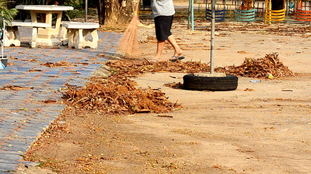 janitor with broom sweeping fallen leaves - sweeping stock videos & royalty-free footage