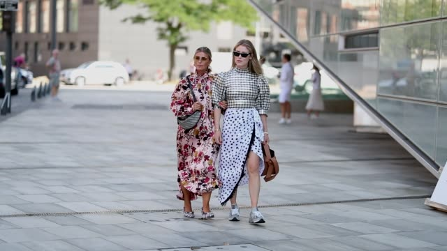 stockvideo's en b-roll-footage met janka polliani wearing dress with floral print and annabel rosendahl wearing silver checked top white skirt with slit and black dots print are seen... - jurk