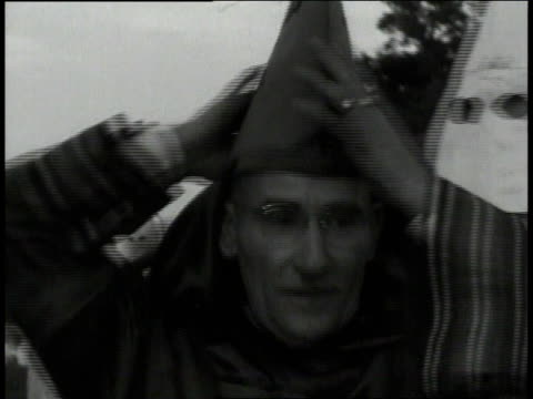 vídeos de stock, filmes e b-roll de january 1 1949 montage grand wizard putting his hood on with other klan members in georgia / united states - ku klux klan