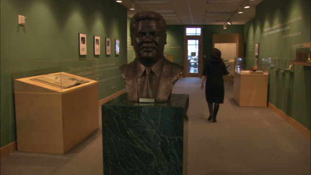 vidéos et rushes de january 1 2008 ws woman walking down a hallway past a bust on a pedestal / chicago illinois united states - représentation masculine