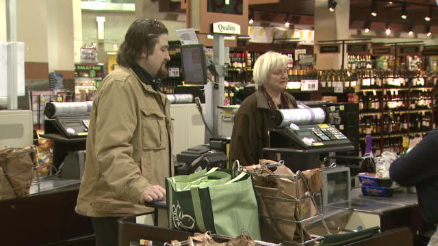 january 1, 2010 customers talking in grocery line at harris teeter food market, some carrying reusable shopping bags / washington, d.c., united states - reusable bag stock videos & royalty-free footage
