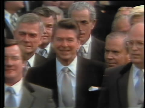 vídeos de stock e filmes b-roll de january 20, 1981 ronald reagan + crowd approach podium + shakes hands with carter + mondale - 1981