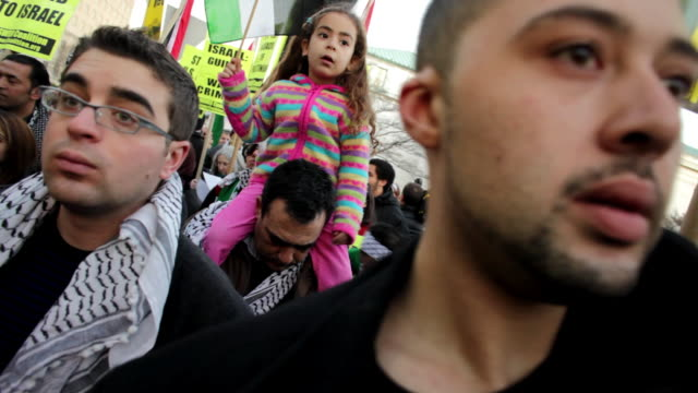 January 23 2009 CU Men listening to speaker during protest against Israel's attack on Gaza Strip as man holds daughter on shoulders behind them/...