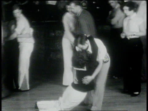 vídeos de stock e filmes b-roll de january 26, 1931 montage exhausted endurance dancers leaning on partners and collapsing / chicago, illinois - 1931