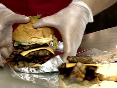 january 3 2003 zo employees preparing hamburgers in five guys burgers and fries / united states - hamburger stock videos and b-roll footage