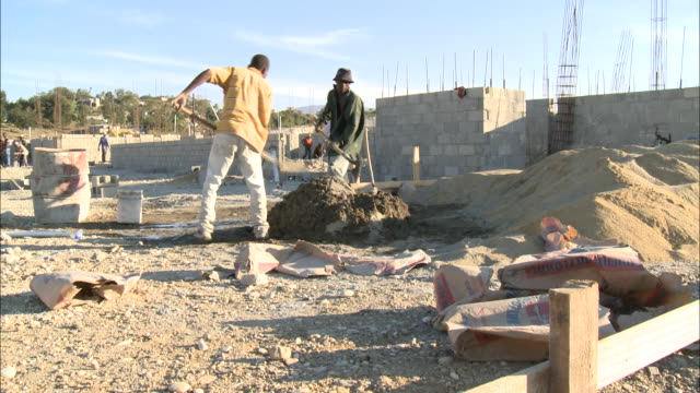 january 4 2011 montage workers digging into dirt pile at construction site / mirebalais haiti - 2010 stock videos & royalty-free footage