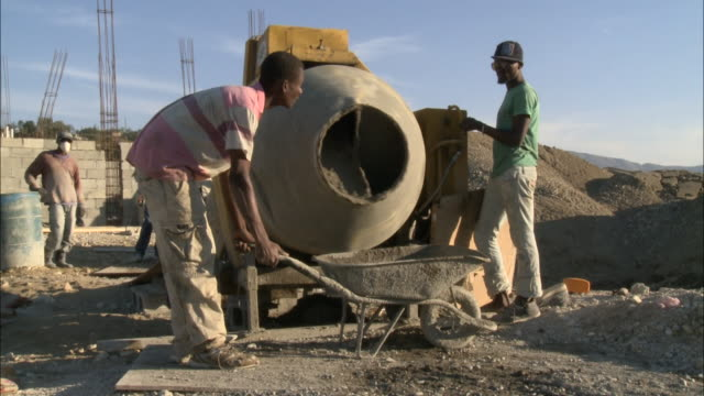 January 4 2011 MONTAGE Workers mixing and wheeling cement at building construction site / Mirebalais Haiti