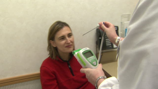 stockvideo's en b-roll-footage met january 5, 2010 doctor obtaining thermometer to take temperature of patient receiving h1n1 vaccine at cvs minute clinic / united states - varkensgriep