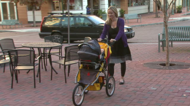 january 5 2010 ts mother pushing baby stroller across pavement past benches and tables in outdoor shopping area / united states - centro commerciale suburbano video stock e b–roll