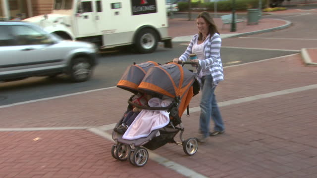 january 5 2010 ts mother pushing double stroller opening door and entering a store in outdoor shopping area / united states - centro commerciale suburbano video stock e b–roll