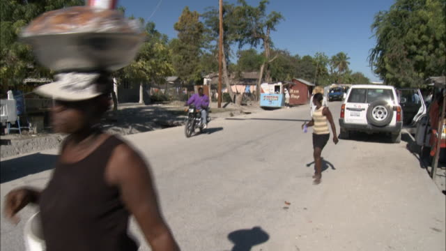 january 5, 2011 montage street scene with locals walking and biking, and a colorful banner strung high across the road about cholera / mirebalais,... - vibrio stock videos & royalty-free footage
