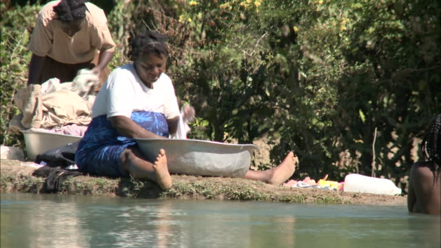 january 5 2011 montage villagers washing clothes and bathing in river / mirebalais haiti - jungen stock-videos und b-roll-filmmaterial