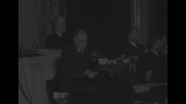 vídeos de stock e filmes b-roll de vs united states congressmen applauding / ms us president franklin delano roosevelt speaking from rostrum microphones before him with abc nbc and cbs... - franklin roosevelt
