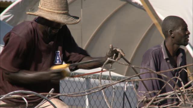 vídeos y material grabado en eventos de stock de january 6, 2011 montage workers sawing metal and clearing debris from hill of rubble / haiti - formato buzón