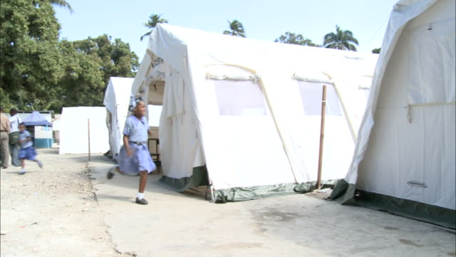 january 6 2011 ts students running around line of white tents made into makeshift classrooms / haiti - resourceful stock videos & royalty-free footage