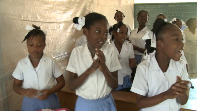 january 6 2011 pan students singing and clapping in classroom / leogane haiti - save the children stock videos & royalty-free footage