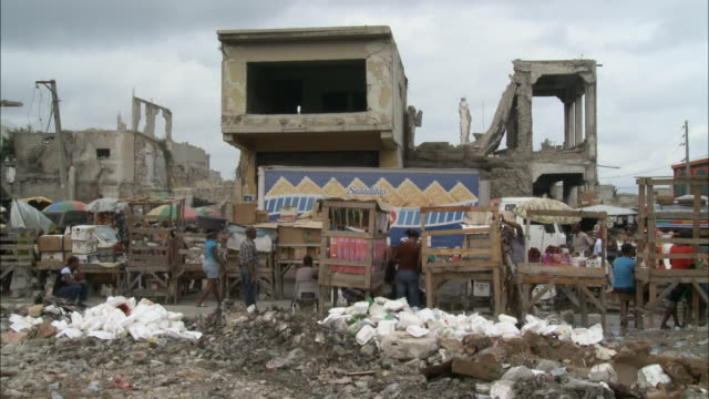 vídeos de stock, filmes e b-roll de january 7 2011 la pedestrian and vehicle traffic passing through outdoor market of makeshift wooden stalls surrounded by heaps of rubble in the... - 2010
