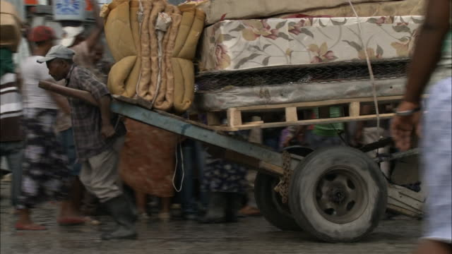 january 7 2011 ts pedestrian pulling makeshift cart loaded with box springs mattress and bedding along busy street congested with vehicle and foot... - ポルトープランス点の映像素材/bロール